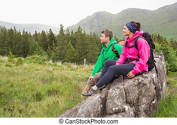 Couple sitting on a rock admiring
