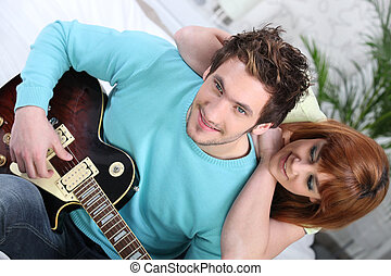 Couple sitting on a sofa with an electric guitar