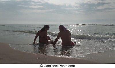 Couple sitting on beach taking photo with smart phone at sunrise.