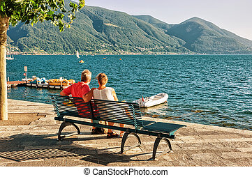 Couple sitting on bench in Ascona in Ticino Switzerland -...