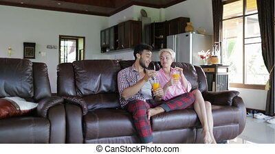 Couple Sitting On Coach In Living Room Drink Orange Juice, Young Man And Woman In Morning Talking Modern Studio Apartment Interior