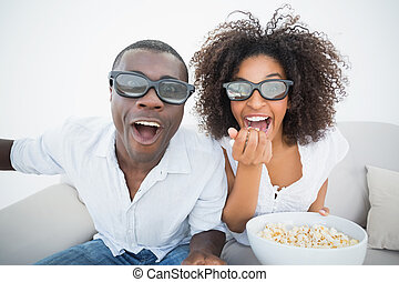Couple sitting on couch together watching 3d movie at home ...