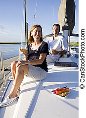 Couple sitting on deck of boat enjoying drink - Mid-adult...