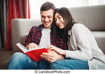Couple sitting on floor and looks at book together