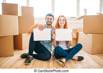 Couple sitting on floor with empty paper sheets