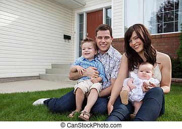 Couple Sitting on Grass With Their Children
