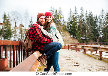 Couple sitting on old bridge in the forest