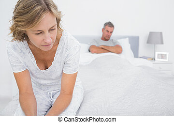 Couple sitting on opposite ends of bed after a fight at home...
