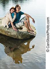 Couple sitting on rock sunset by lake