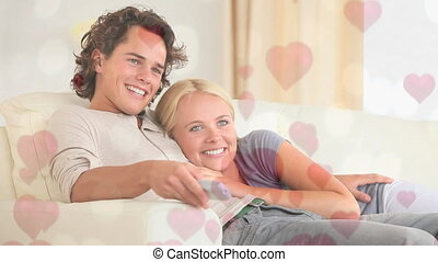 Couple sitting on sofa in living room with hearts