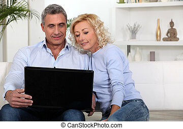 Couple sitting on sofa looking at laptop
