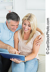 Couple sitting on sofa looking at the tablet