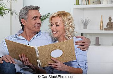 couple sitting on sofa skimming through family album