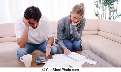 Couple sitting on the couch while checking their bills