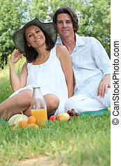Couple sitting on the grass eating fruit