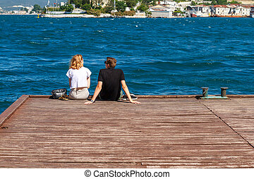 couple sitting on the pier on a Sunny day