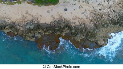 Couple sitting on the rocky sea coast 4k - High angle view...