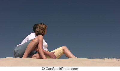 Couple sitting on the sand and looking to the right