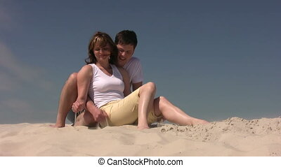 Couple sitting on the sand, he strew the sand