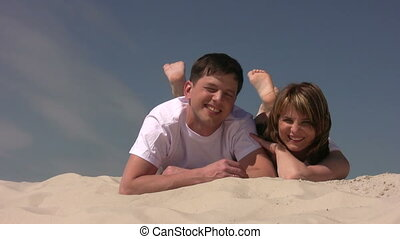 Couple sitting on the sand, shaking their legs