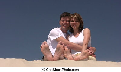 Couple sitting on the sand, showing their heels