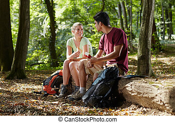 couple sitting on trunk and eating snack after trekking -...