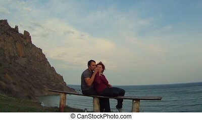 Couple sitting outdoors - Young couple drinking from a glass...