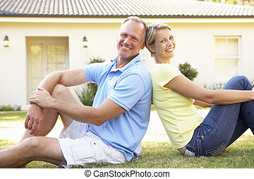 Couple Sitting Outside Dream Home