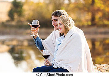 couple sitting together by a lake