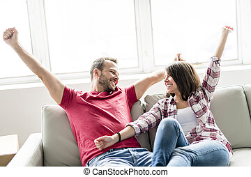 Couple sitting together on sofa at home happy to move from home