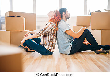 Couple sitting with backs to each other, new home