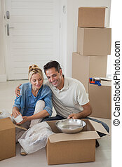 Couple sitting with boxes in new house