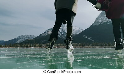 Couple skating together on a frozen lake