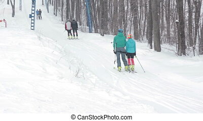 Couple skiers Ski-lift on a small track for ski.