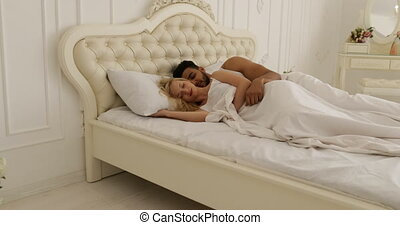 Couple sleep lying on bed man hug woman home white modern bedroom