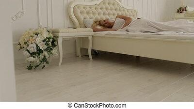 Couple sleep lying on bed morning wake up happy smile man hug woman home white bedroom