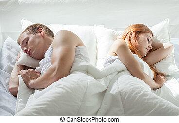 Couple sleeping back to back