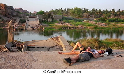 Couple of tourists sleeping by ruined bridge over calm river
