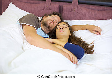 Couple sleeping in bed hugged relaxed