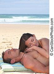 Couple sleeping on the beach