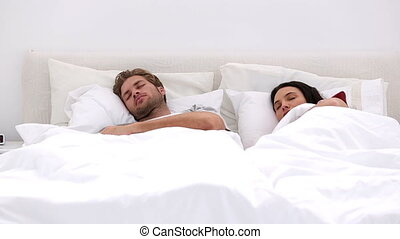 Couple sleeping peacfully with partner pressing snooze on...
