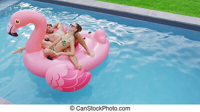Couple sleeping together on inflatable tube in swimming pool 4k