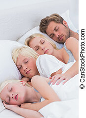 Couple sleeping with their children
