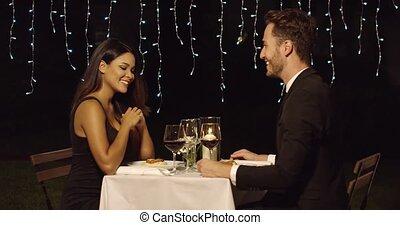 Couple smiles across restaurant dinner table