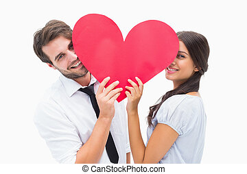 Couple smiling at camera holding a heart on white background