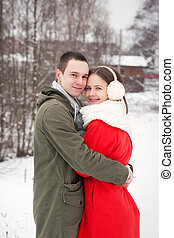 Couple smiling with perfect teeth hugging and looking at camera in winter in a forest