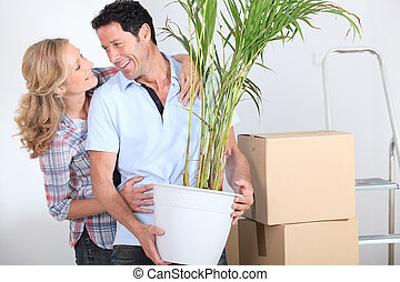 Couple smiling with plant