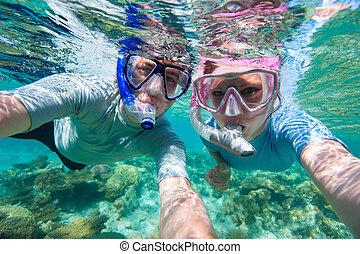 Underwater photo of a couple snorkelling in ocean