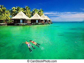 Couple snorkling in lagoon with over water bungalows -...