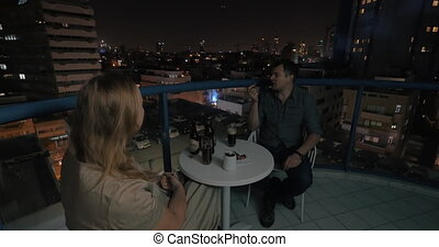 Couple spending evening in rooftop cafe of night Tel Aviv -...
